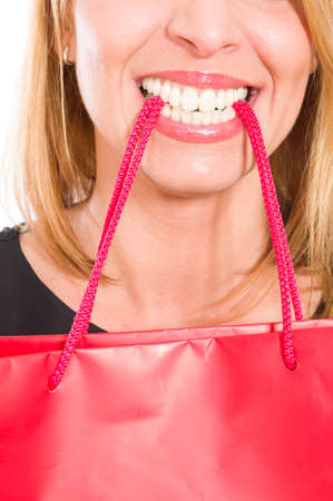 sopping: Sopping woman holding red paper bag with her teeth Stock Photo