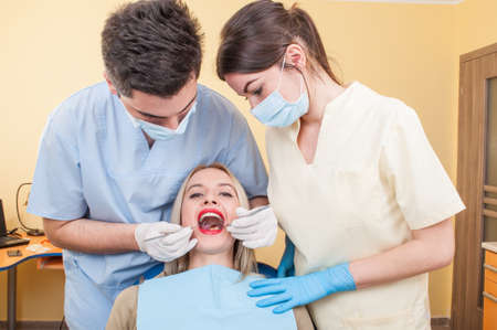 Hygienist working with assistant on a beautiful woman patient with perfect teeth photo