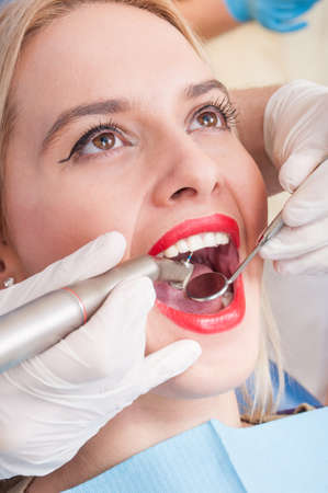 dentist drill: Beautiful woman having dental exam and drilling or cleaning  procedure