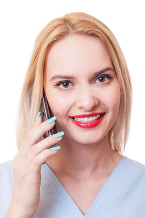 contactus: Smiling woman doctor talks on smartphone. Contactus concept on white background.