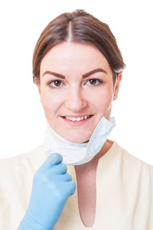Medical nurse or dentist assistant uncovering the mouth from protective surgical mask