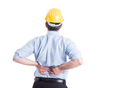 dolor espalda: Ingeniero o arquitecto sintiendo el dolor de espalda después de un largo día de trabajo Foto de archivo