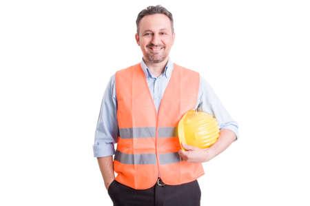 誇りに思って、自信を持って、成功した請負業者、職長またはベストと黄色いヘルメットを身に着けているビルダー