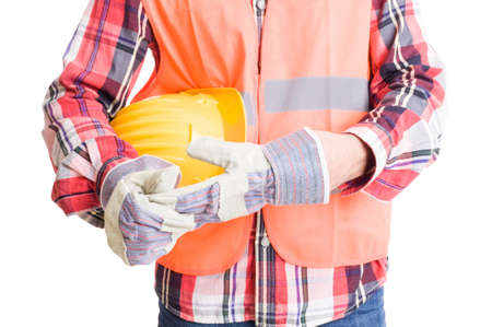 underarm: Builder or construction worker pulling out glove after work while holding helmet underarm