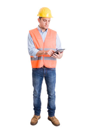 Modern engineer using a wireless tablet to check construction project or tasks