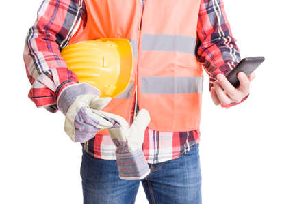 construction workers: Modern builder checking smartphone while holding helmet underarm Stock Photo