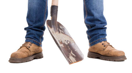 dirty feet: Builder feet and dirty shovel. Wide picture isolated on white background Stock Photo