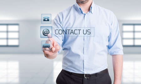 contactus: Business man pressing contact us button on transparent touch screen. Support, assistance or feedback concept