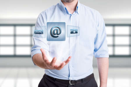 contactus: Business man holding futuristic contact us floating icons. Support, assistance or feedback concept