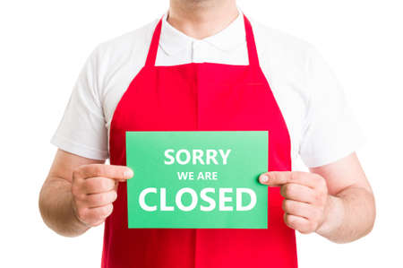 closed sign: Sorry we are closed sign hold by supermarker employee or worker
