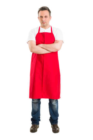 Confident butcher or supermarket worker wearing red apron