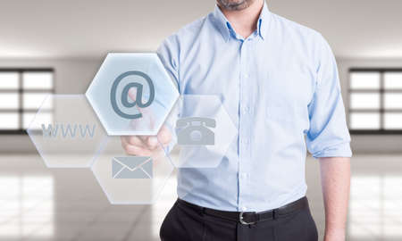contactus: Contact us using email concept with man pressing button on transparent futuristic touch screen
