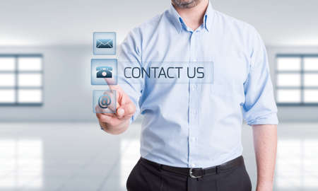 Hitech or high tech contact us concept with man pressing button on transparent screen display