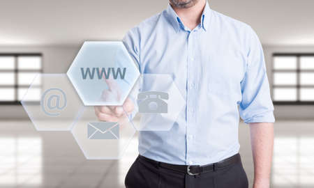 contactus: Contact us using online website  concept with man pressing button on transparent futuristic touch screen