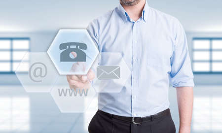 Contact us using phone  concept with man pressing button on transparent futuristic touch screen