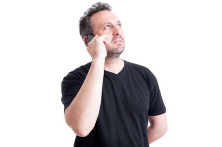 visionary: Modern man thinking while talking on smartphone and looking up like a visionary male