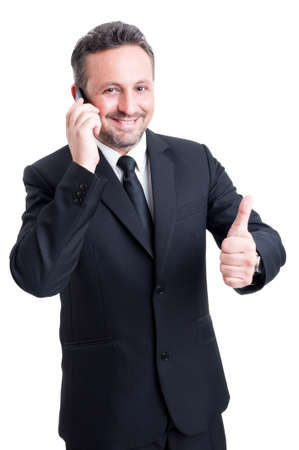 Business man talks on the phone and shows thumb up. Confident salesman concept photo