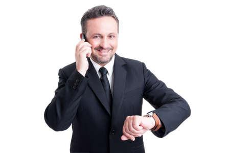 puntualidad: Hombre de negocios con la puntualidad de comprobar el reloj mientras habla por tel�fono