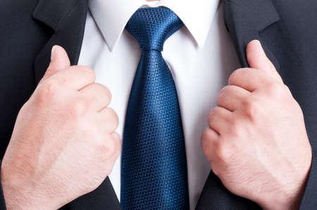 Business man borst zo machtige leider concept. Zwart pak, wit overhemd en blauwe stropdas