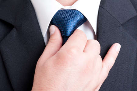 Successful manager and elegant politician fixing or adjusting blue tie