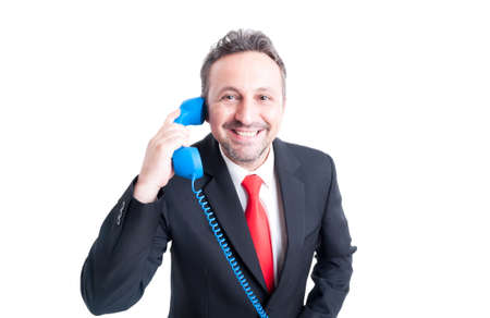 answering phone: Smiling sales man answering phone and looking at the camera