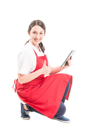 thumbup: Hypermarket female worker showing thumb up while holding wireless tablet