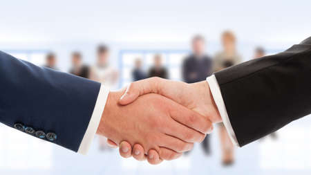 deals: Businessmen hand shake with business people in background. Congratulation or cooperation concept Stock Photo