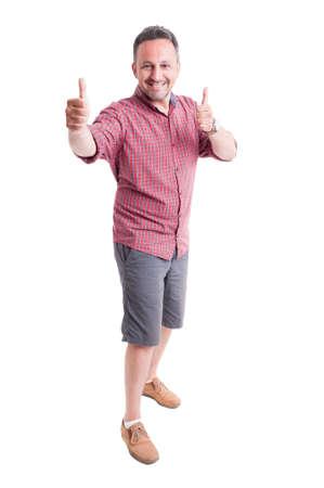 thumbsup: Cheerful man showing thumbs up. He wears shorts and short sleeve shirt