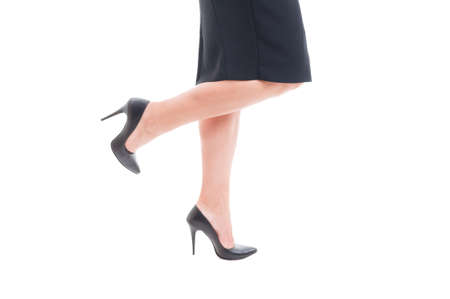 Business woman legs with high heels black leather shoes and skirt isolated on white background