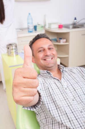 relajado: Paciente masculino relajado en la silla del dentista mostrando gran similares o pulgar Foto de archivo