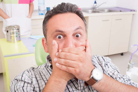 mouth pain: Scared man at dentist covering his mouth. Pain in dental office concept or idea Stock Photo