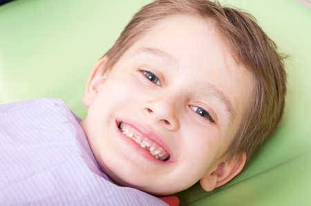 no fear: Smiling child with happy face on dentist chair or office. Kid with no fear of dentist concept
