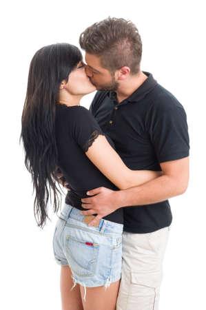 enamorados besandose: Hermosa morena pareja bes�ndose y abraz�ndose en el fondo blanco del estudio