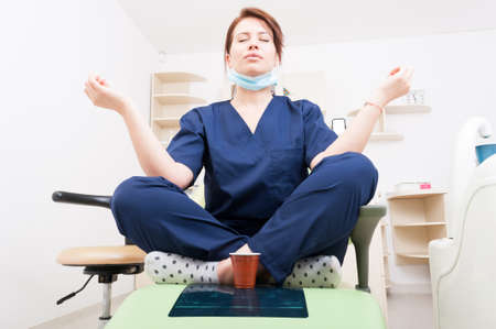Dentist woman meditating with yoga and lotus position. Coffee break and relaxing lifestyle as a doctor