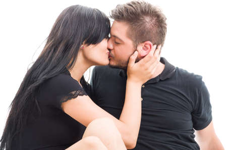 kissing mouth: Brunette couple kissing on the mouth sitting on white studio background Stock Photo