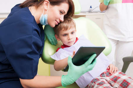 Modern dentist use wireless tablet with kid patient. Child having fun and playing in dentist chair