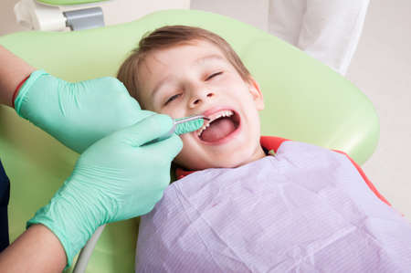 Relaxed kid in dentist chair ready for checkup procedure