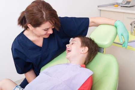 odontologa: Relájese niño de risa en silla de dentista y divertirse con Doctor amigable payful Foto de archivo