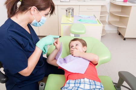 calming: Woman dentist calming kid patient with games in dental office Stock Photo