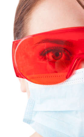 half face: Half face of dentist woman wearing mask and protective glasses on white background Stock Photo