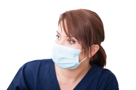 Woman doctor looking left and wearing mask isolated on white background Stock Photo