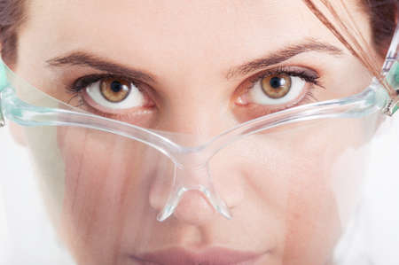 kinky: Closeup of eyes of dentist woman wearing protective screen, shield of transparent plastic