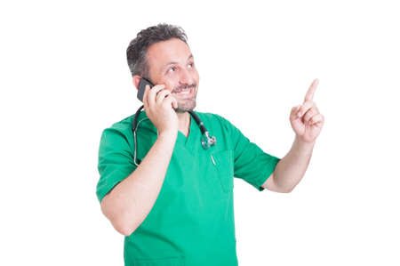 contactus: Doctor talking on the phone and smiling while looking and pointing finger up