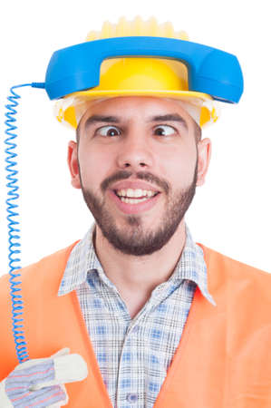 crosswise: Funny contact person of construction company holding phone on helmet and eyes crosswise