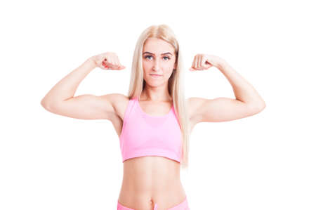 femme blonde: Sexy fitness girl flexing muscle arms isolated on white background. Blonde sporty girl wearing pink sportswear