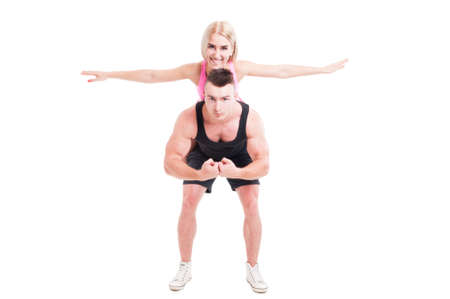 ful: Fitness couple of trainers having ful with piggyback isolated on white background Stock Photo