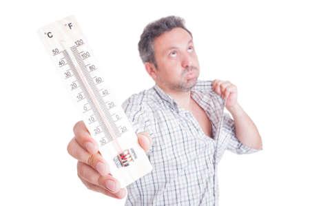 caliente: Hombre sudoroso que sostiene el termómetro como concepto de calor del verano aislado en blanco