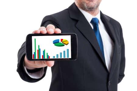 Marketing manager die smartphone met het kweken van financiële grafiek en cirkeldiagram op wit wordt geïsoleerd