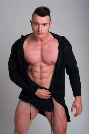 naked male: Naked male model posing in studio wearing a black hoodie