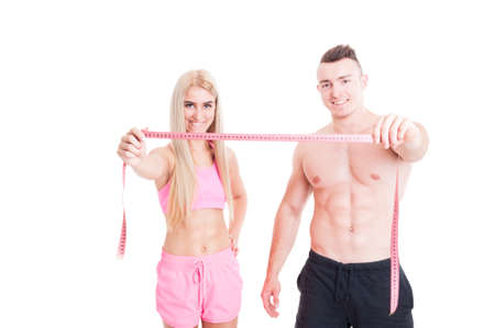 Healthy fitness couple holding meter or centimeter as weight loss concept isolated on white